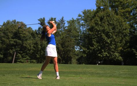 Freshman Molly Hixon swinging the golf club during the match.
