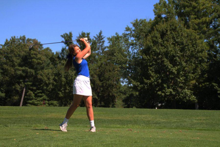 Freshman Molly Hixon swinging the golf club during the match.
