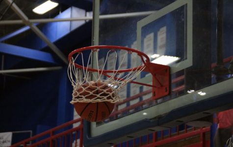 A student shot a basketball into the hoop at the Martinsville High School gym.