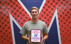 Miles Anderson is holding his Athlete of the Month Award.