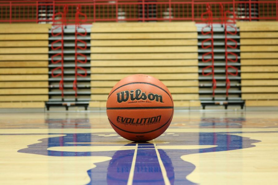 A basketball sitting in the center of the court in the John R. Wooden Gymnasium.