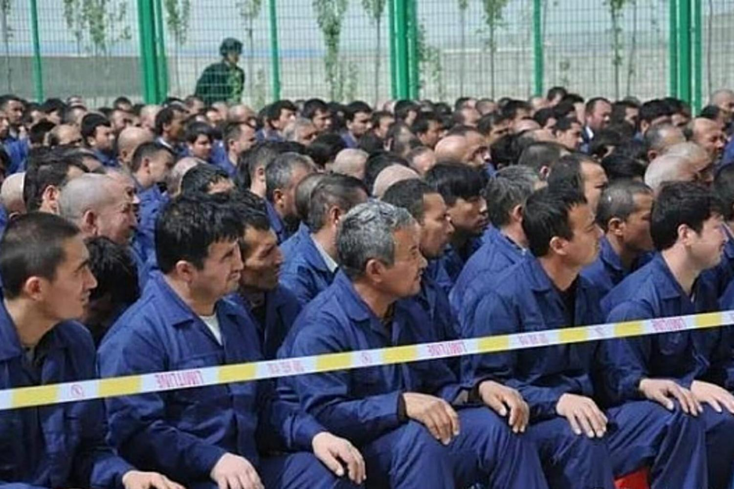 Detained Muslims sit waiting in a reeducation camp in China.
