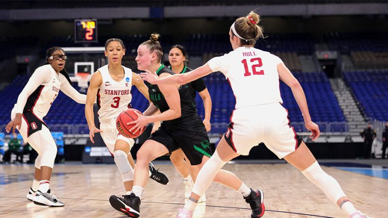Maria Carvalho #3 of the Utah Valley Wolverines drives past Lexie Hull #12 and Anna Wilson #3 of the Stanford Cardinal in the first round game of the 2021 NCAA Women