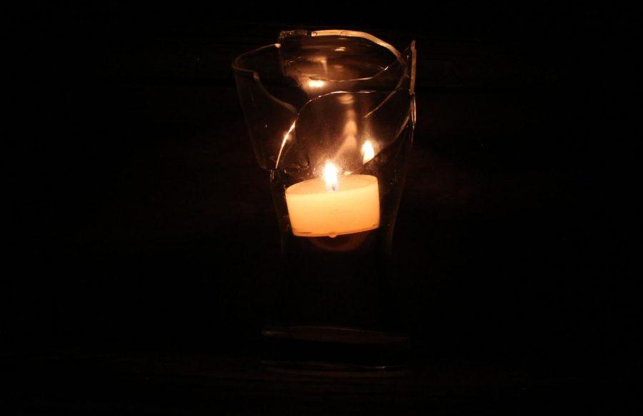 A+candle+burns+inside+a+broken+glass+