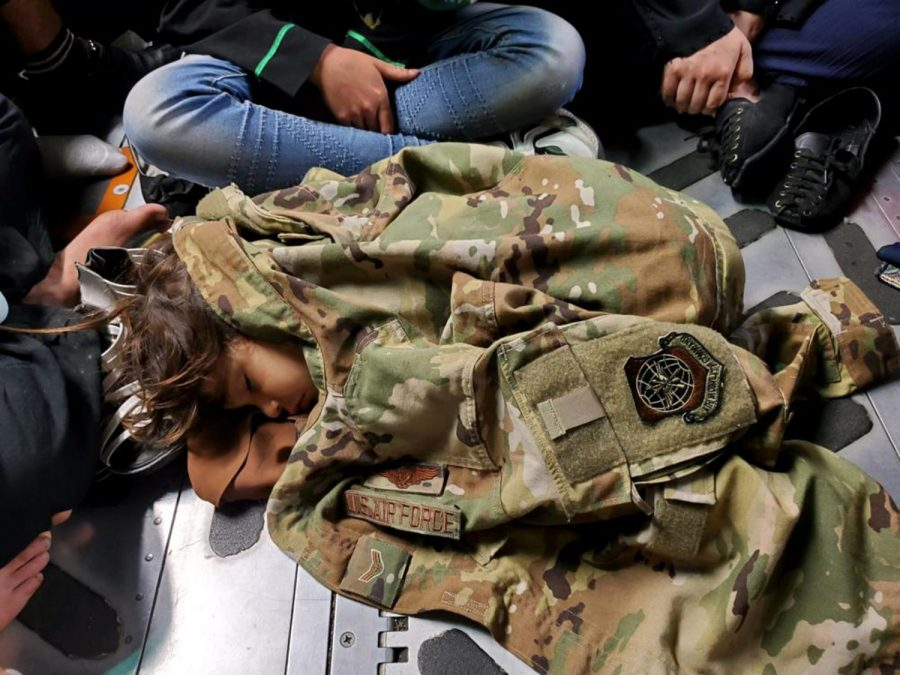 An Afghan child sleeps peacefully under the warmth of an Air Force soldier's uniform.
